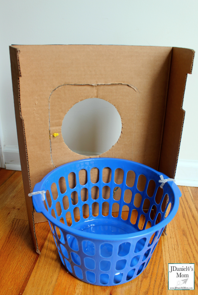 A DIY Cardboard Kids' Washing Machine - It is great for pretend play or a part of a learning activity for kids. It has a removable laundry basket. It is great for holding the object placed in the washing machine.