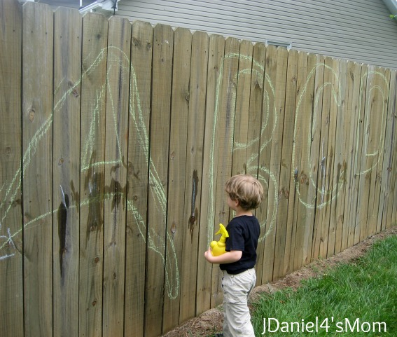 Drawing with Chalk on a Fence