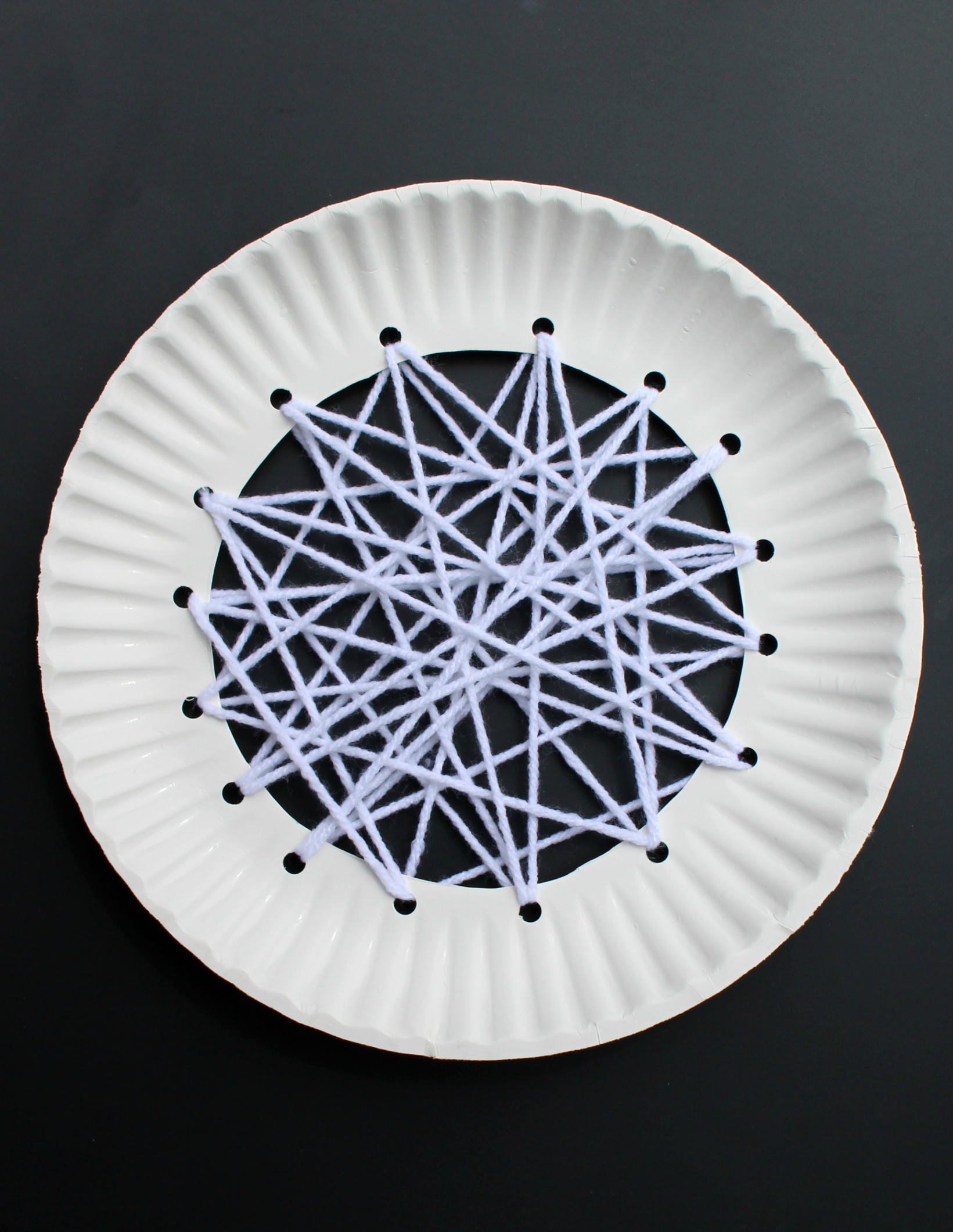Apple Craft That Works on Fine Motor Skills - White Yarn Weaving in the Middle of the Plate