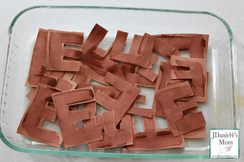 Capital letters E made out of brown paper.